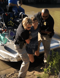 A distressed person being dragged out of a boat by two police officers